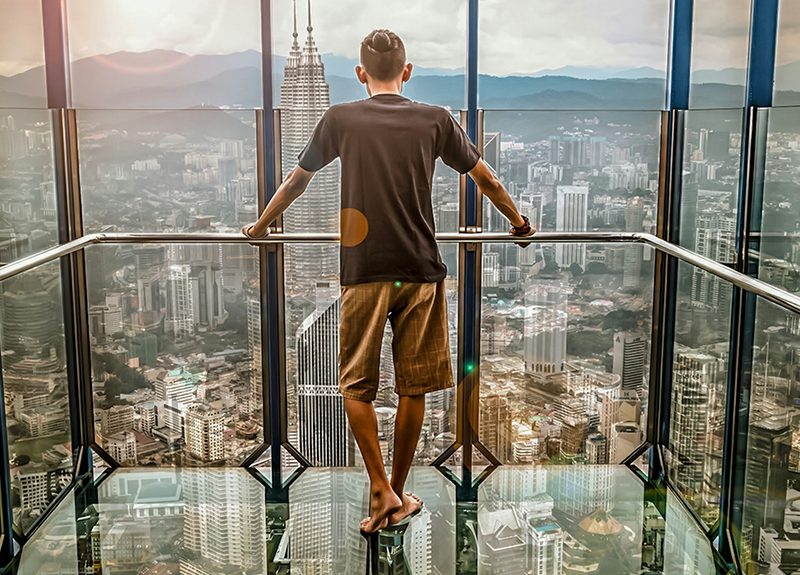 Man standing in glass lift over large city