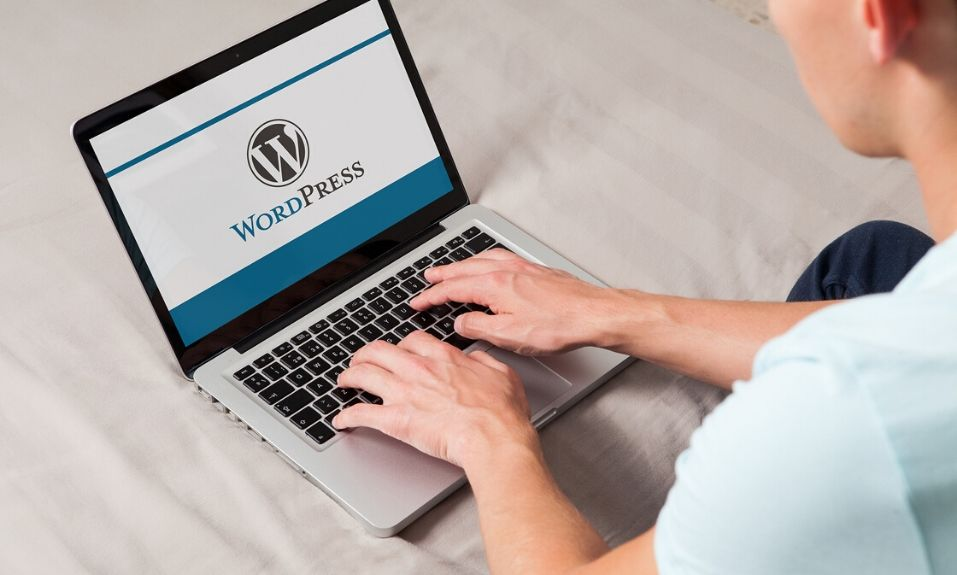 Wordpress brand logo on computer screen. Man typing on the keyboard. WordPress is a free and open-source blogging tool and a content management system (CMS).