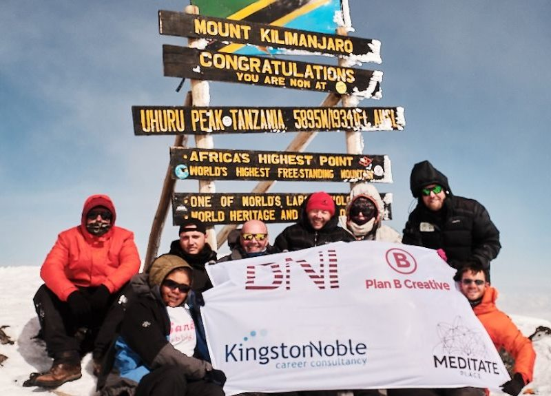 BNI Birmingham Members atop of Mount Kilimanjaro displaying a banner featuring Plan B Creative