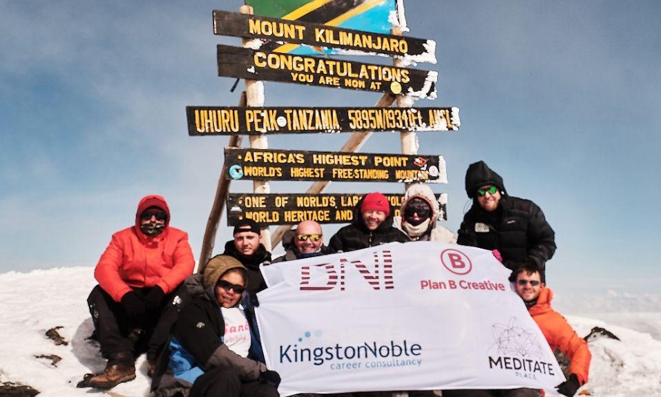 BNI Birmingham Members atop of Mount Kilimanjaro displaying a banner featuring Plan B Creative